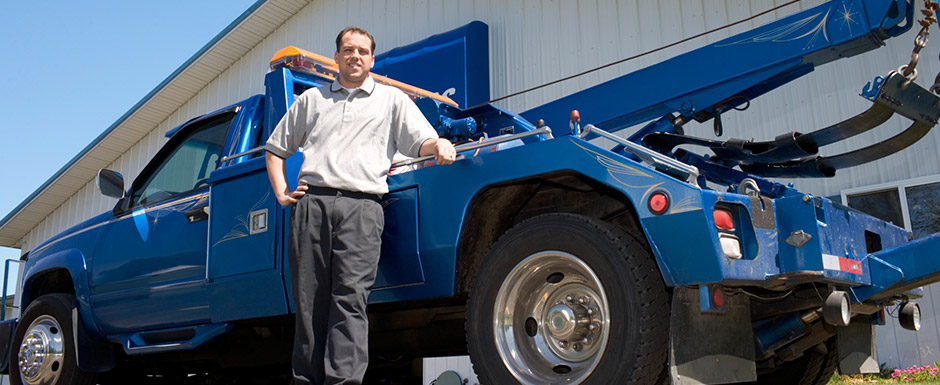 Man standing at his blue tow truck